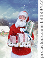 A smiling Santa Claus in front of the house holding a Christmas gift in the snowy landscape 63139422
