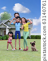 A smiling family standing in front of the house under the blue sky 63140761