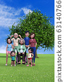 Smiling family standing in front of big tree in park 63140766