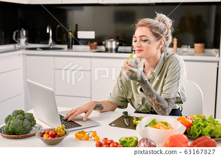 Leisure at Home. Young tattooed woman standing at kitchen watching video on laptop eating vegetable laughing cheerful while cooking 63167827