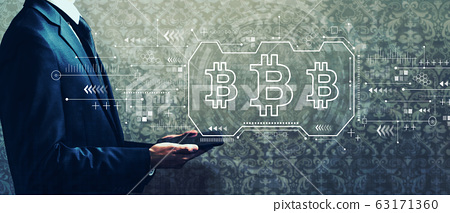 Bitcoin theme with businessman holding a tablet 63171360