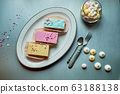 Beautiful delicate shortbread cakes with icing of delicate colors. Tea party for the holiday. Confectionery art.The view from the top, the background is silver. 63188138