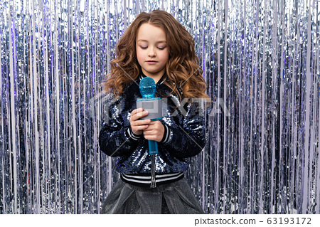 stylish girl with a microphone in her hands on a shiny tinsel background 63193172