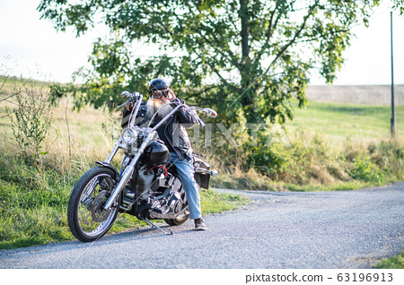 A senior man traveller with motorbike and goggles in countryside. 63196913