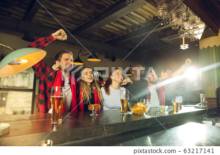 Sport fans cheering at bar, pub and drinking beer while championship, competition is going 63217141