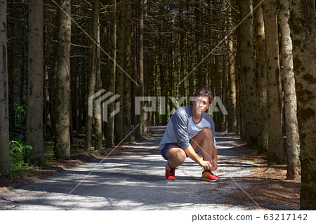 Young man with an athletic figure in shorts, tying shoelaces before running through the forest 63217142