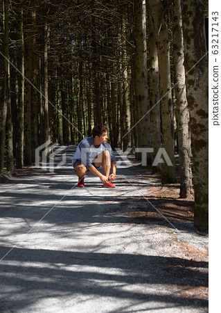 Young man with an athletic figure in shorts, tying shoelaces before running through the forest 63217143