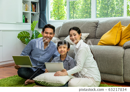 Happy Asian parent sitting together with boy on 63217834