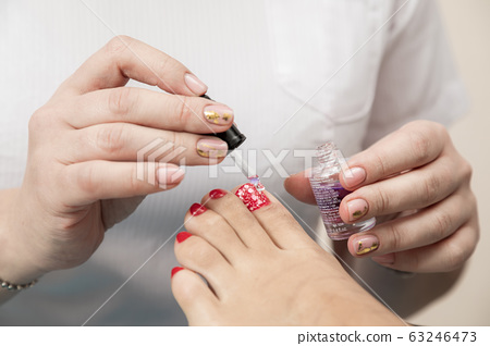 Pedicure Master does the procedure to the client 63246473