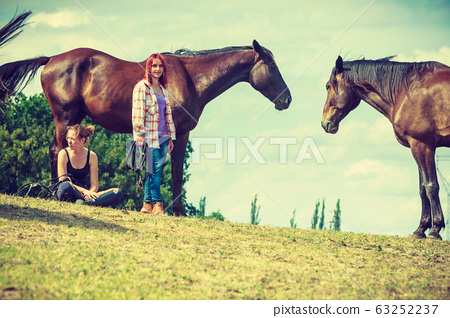 Jockey woman sitting with horse on meadow 63252237