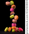 Flying french colorful macaroons on wooden table isolated on black 63260804