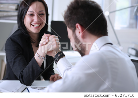 Woman and man in suit hold hands in wrestle 63271710