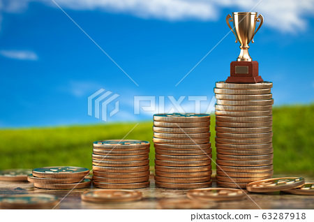 Trophy cup on stacks of coin.   Concept of 63287918