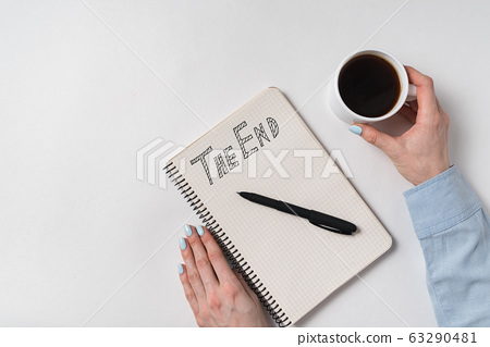 Notepad with words the end. Female hands with Cup 63290481
