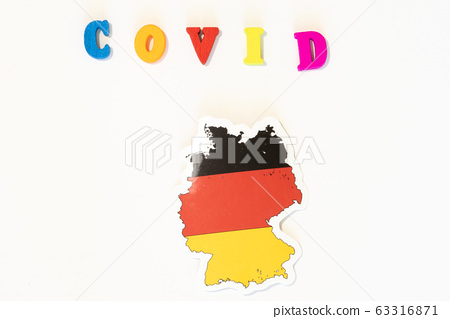 Germany national flag on a white background with the inscription Covid made with letter board. Coronavirus is a pandemic virus originating in China 63316871