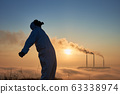 Environmentalist with smoking thermal chimneys on background. 63338974