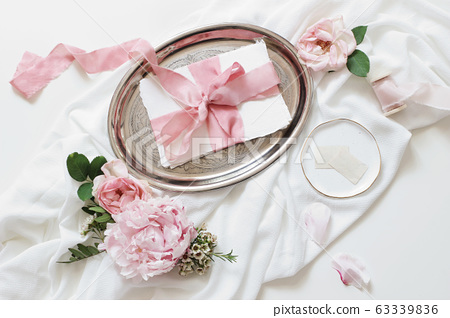 Feminine wedding, birthday mock-up scene. Blank paper greeting cards, pink roses, silk ribbons, peony flowers on silver plate, White table background. Light, shadow play. Flat lay, top view 63339836