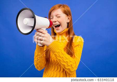 red-haired teenage girl screaming with closed eyes to the news loudspeaker on a blue studio 63340118