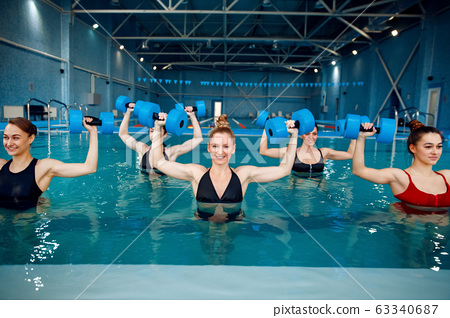 Aqua aerobics, exercise with dumbbells in the pool 63340687
