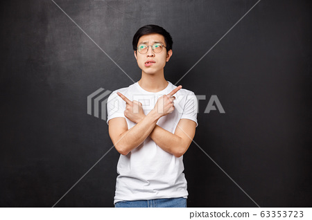 Indecisive silly asian guy dont know what choose, pointing fingers sideways left and right at two varitants or products, biting lip hesitant look away as thinking, making decision 63353723