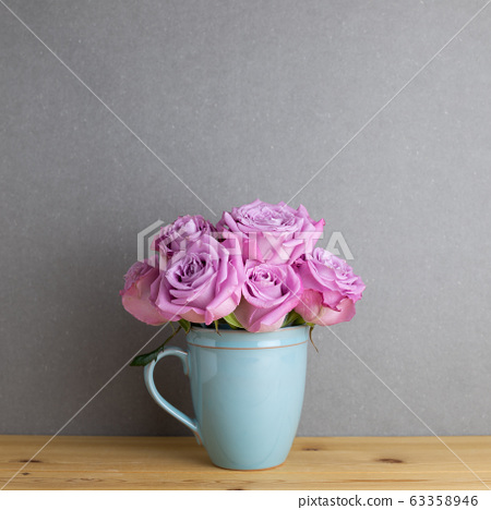 Purple rose flowers in ceramic cup on wooden table with gray background. Spring floral arrangement, copy space 63358946