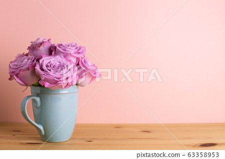 Purple rose flowers in ceramic cup on wooden table with pink background. Spring floral arrangement, copy space 63358953