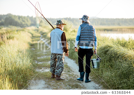 Grandfather with adult son walking near the lake 63368844