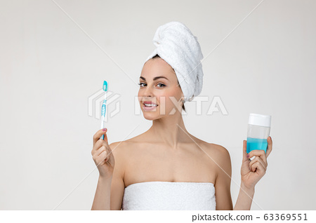 Happy young woman in towel brush her teeth 63369551