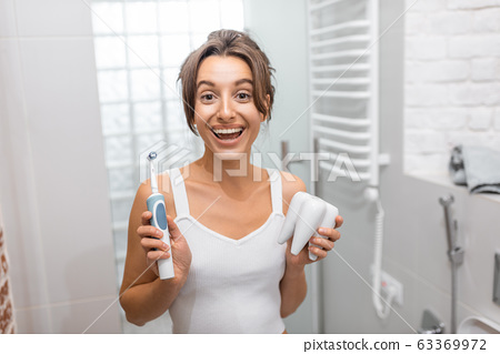 Woman cleaning teeth with electric toothbrush 63369972