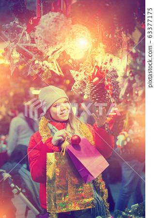 Happy girl chooses Christmas toys on the street market 63377175