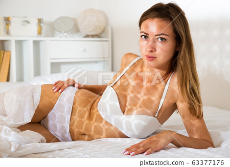 Attractive young woman with long hair lying in bed and smiling 63377176