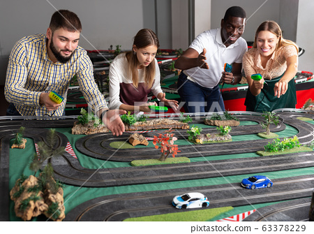 Portrait of friends with slot car racing game 63378229