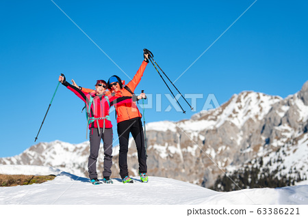 Two climbers conquer the top of a mountain 63386221