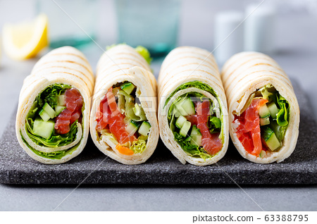 Wrap sandwich, roll with fish salmon and vegetables on cutting board. Grey background. Close up. 63388795