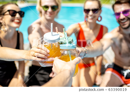 Friends with drinks on the swimming pool outdooors 63390019