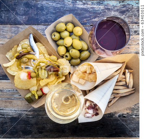 Tapas and pinchos, overhead square shot. Cheese, jamon and olives, gildas and potato chips, with glasses of red and white wine, on a wooden table in an outdoors cafe 63403011