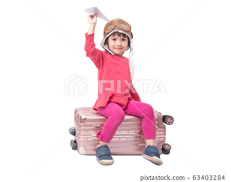 Asian little cute girl 4 years old wear pilot hat and sitting on pink luggage with holding paper airplane isolated on white background.  63403284