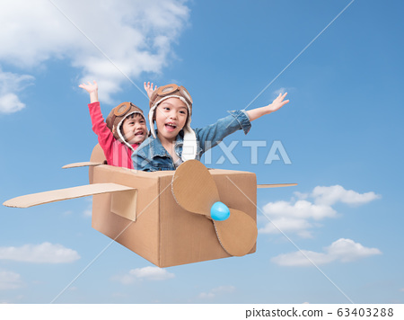 Asian siblings cute girl playing cardboard airplane on blue sky background with clipping path. Two asian children play as pilot on cardboard airplane DIY. 63403288