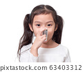 Asian little cute girl 6 years old using asthma inhaler on white background. 63403312