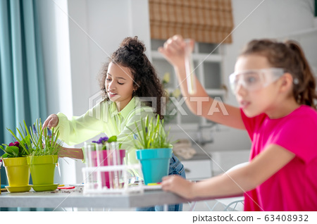 Girl in green shirt near flowerpots, girlfriend with a test tube. 63408932