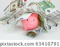 Pink piggy money box in pile of dollar and euro 63410791