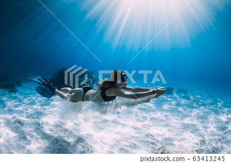 Woman free diver glides with white sand over sandy sea. Freediving underwater in Hawaii island 63413245