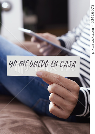 man showing the message I stay at home in spanish. 63416075