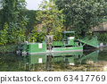 An aquatic weed harvester on a lake. 63417769