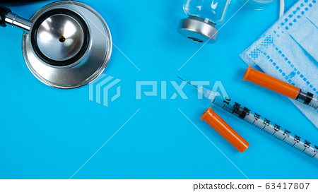 Insulin Vial and Syringe on Blue Background 63417807