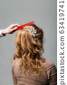 Wave curls hairstyle. Hairdresser making hairstyle 63419741