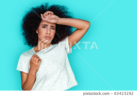 Freestyle. Mulatto girl standing isolated on blue touching head breathing from heat 63423292