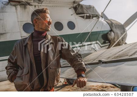 Stylish guy wearing leather jacket near plane 63428507