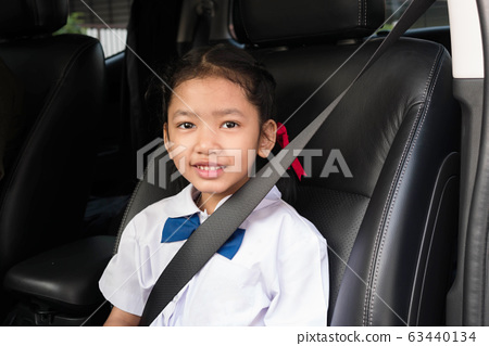 Asian girl wear school uniform sit in the car 63440134