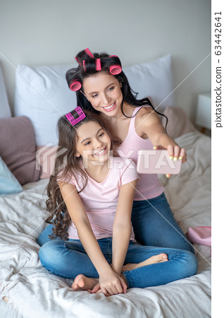 Mom and daughter with hair curlers making selfie 63442641